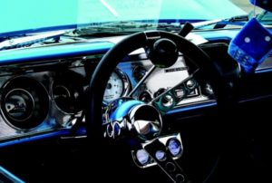 close up of classic steering wheel and dice on rear view mirror Queener Law