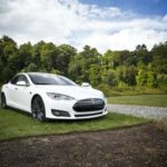 white tesla sports car on display on golf course setting Queener Law
