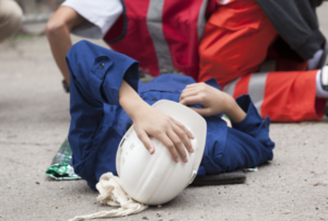 woman lying down holding hard hat after accident Queener Law