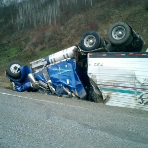 bad accident with totaled bed and turned over semi truck on shoulder of road Queener Law