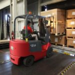 forklift driver getting boxes in warehouse Queener Law