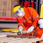 construction worker using drill with proper PPE Queener Law