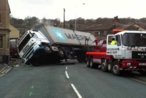 semi truck turned over with tow truck helping Queener Law