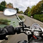 view from motorcycle riders helmet while driving on road Queener Law