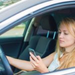 distracted female teenager looking at phone while driving Queener Law