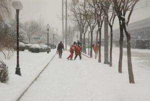 maintenance workers blowing snow off sidewalk while pedestrian walks by Queener Law