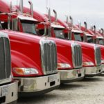 long row of red semi trucks ready to roll Queener Law