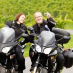 man and woman stop to take selfie on motorcycles Queener Law