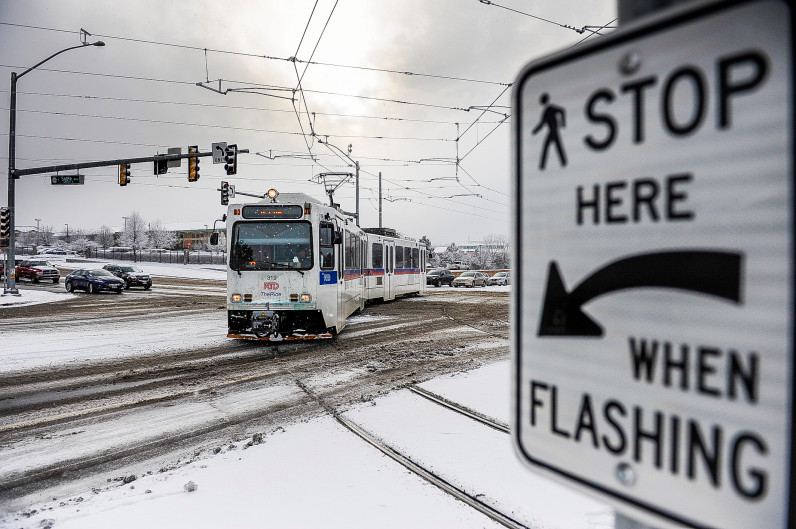 Image of a snowy day in which an RTD train is proceeding properly at the same intersection as the derailment.